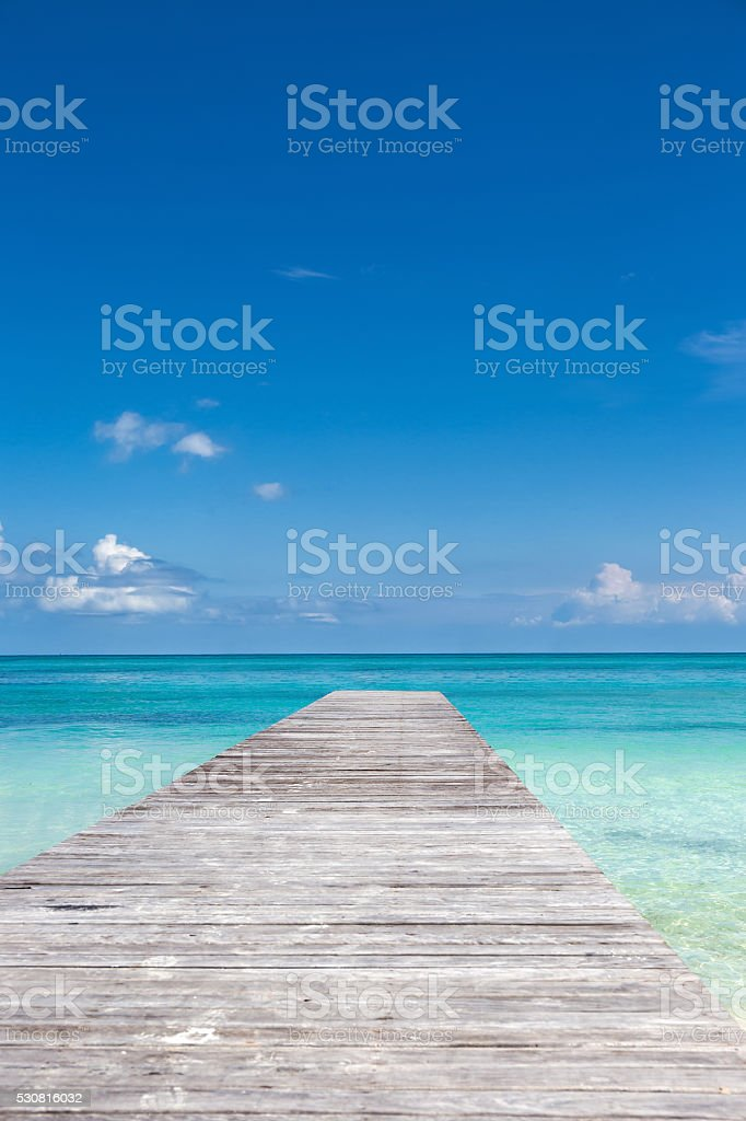 Wooden pier on tropical beach stock photo