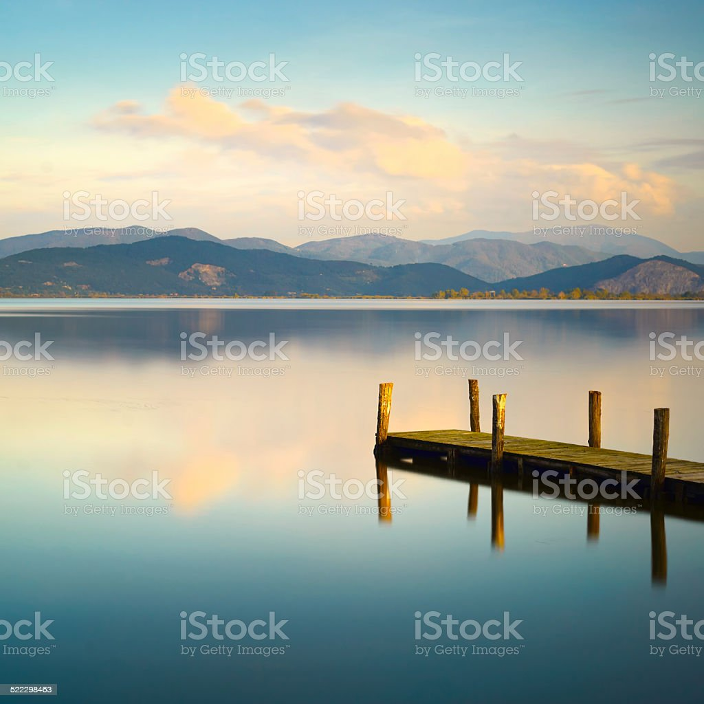Wooden pier or jetty,  blue lake sunset and sky reflectio stock photo