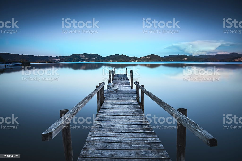 Wooden pier or jetty  blue lake sunset and sky reflection stock photo