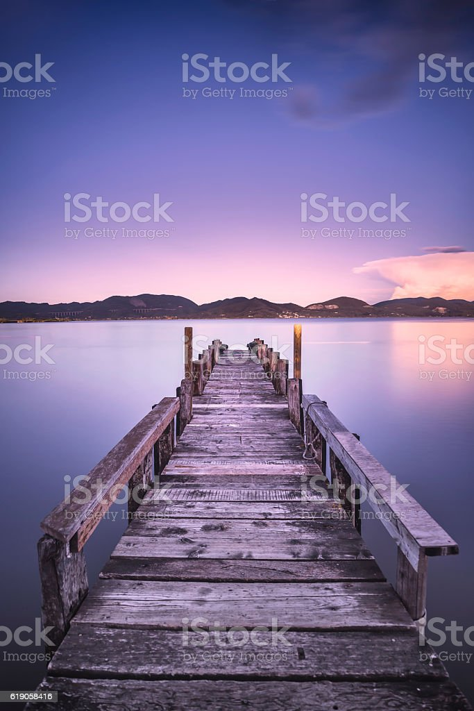 Wooden pier or jetty on  blue lake sunset sky reflection stock photo