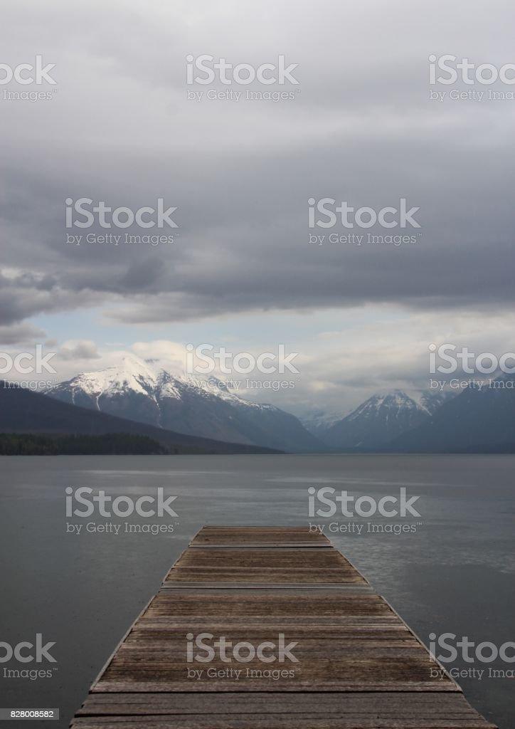 Wooden Pier Overlooking Mountains stock photo