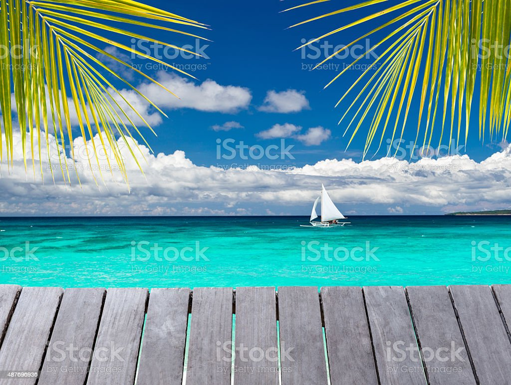 Wooden pier with view on sailboat in the sea stock photo