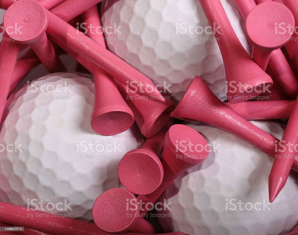 Wooden pink golf tees around three white golf balls  stock photo
