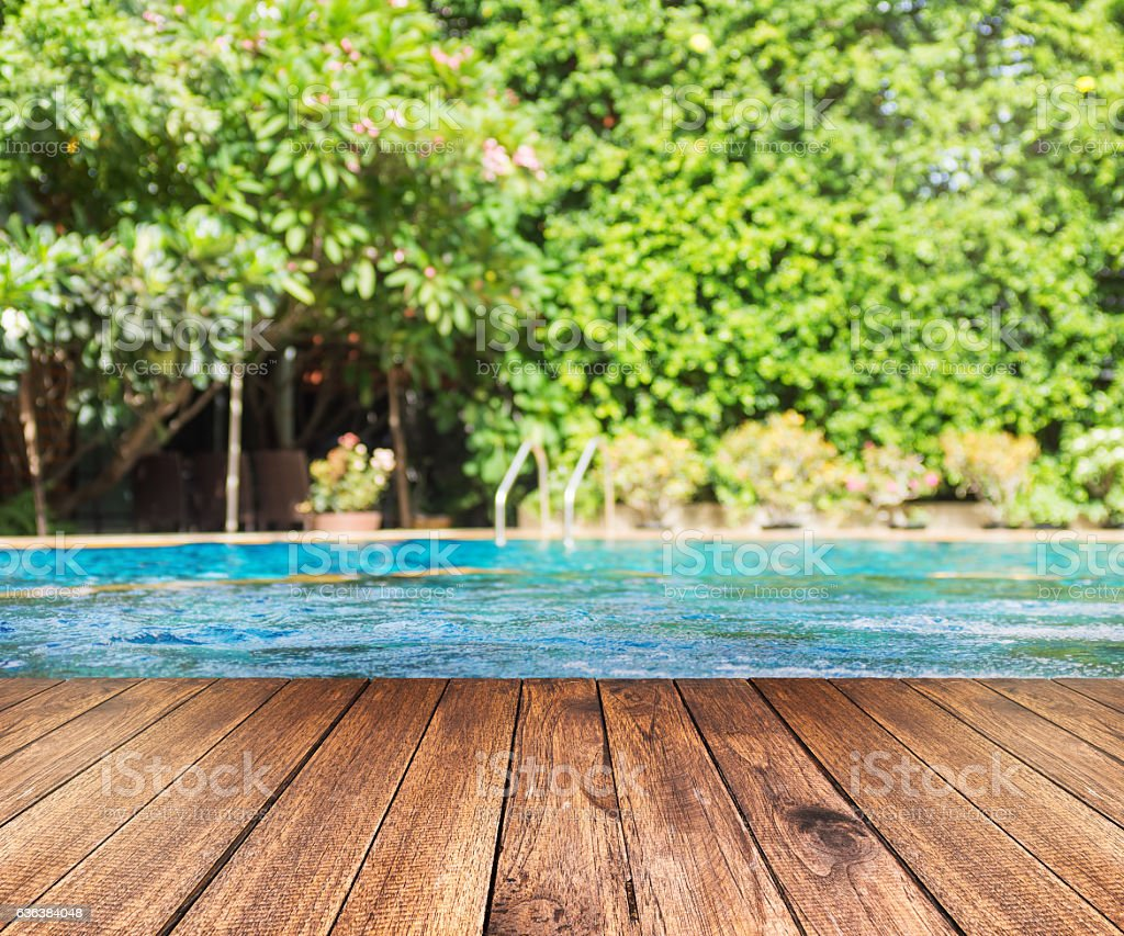 Wooden plank floor against swimming pool with green trees stock photo