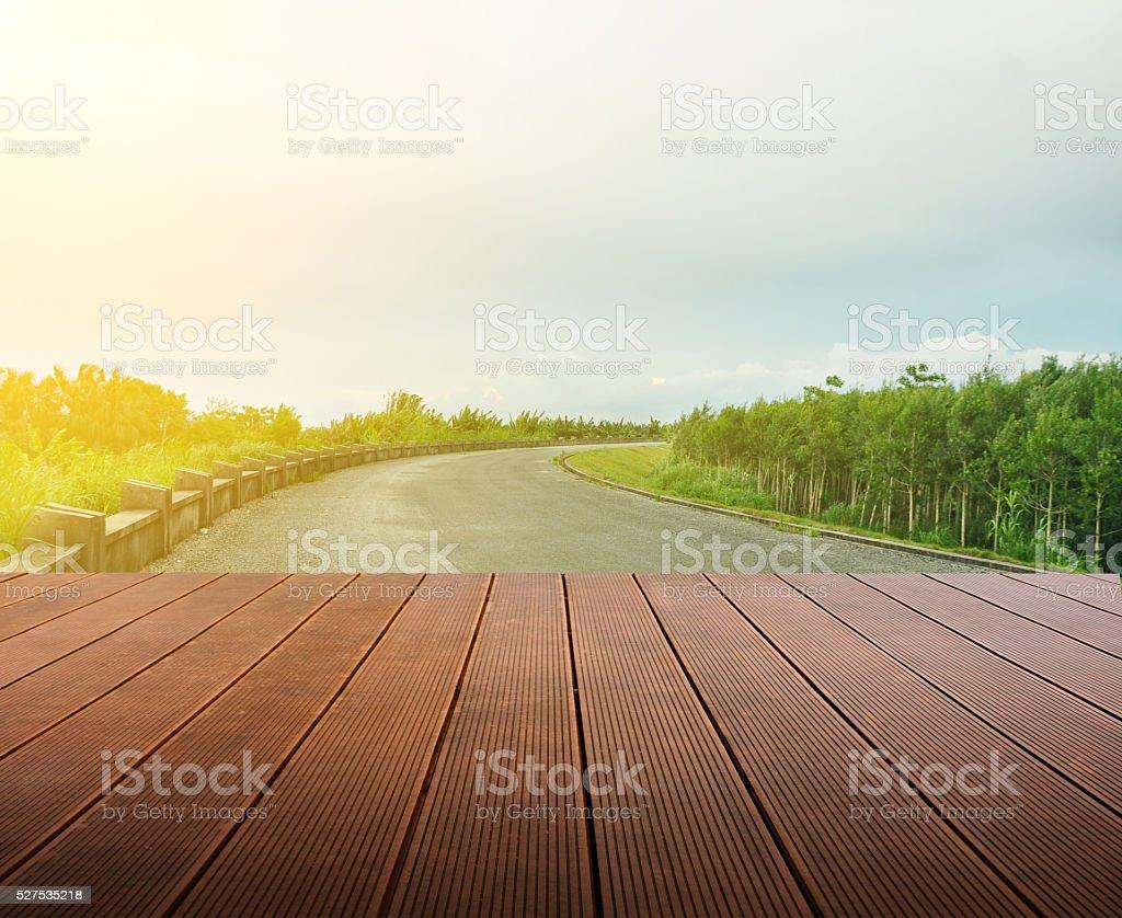 Wooden planks floor background and empty asphalt road. stock photo