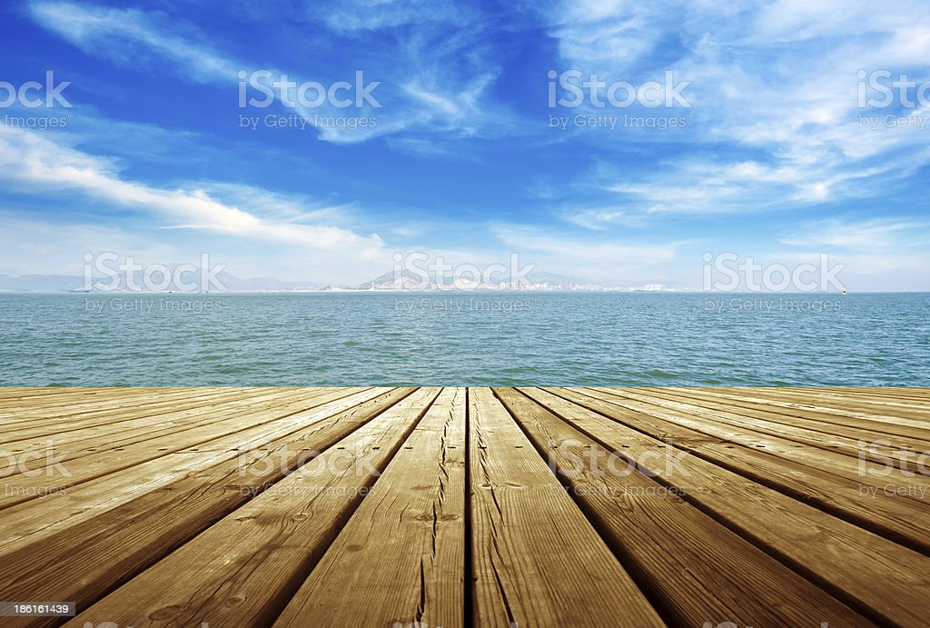Wooden planks of a dock next to water stock photo