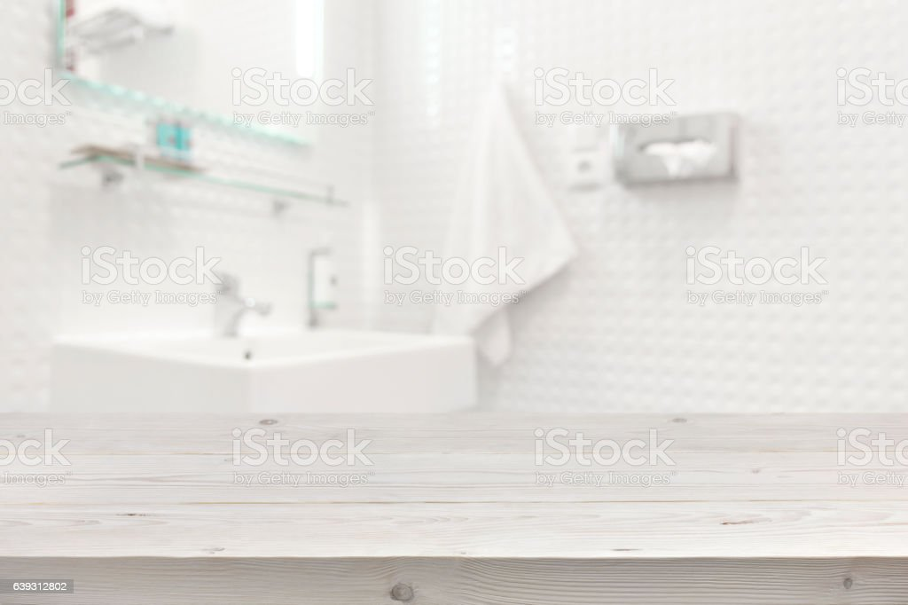 Wooden planks surface and blurred bathroom interior as background stock photo