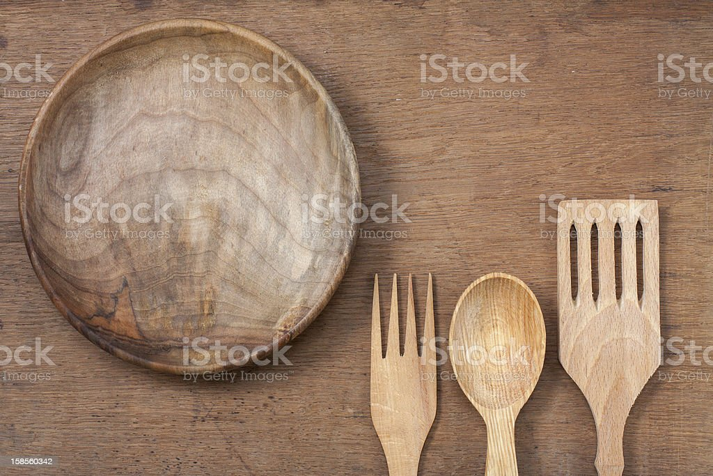 Wooden plate, fork and spoon on oak wood texture background royalty-free stock photo