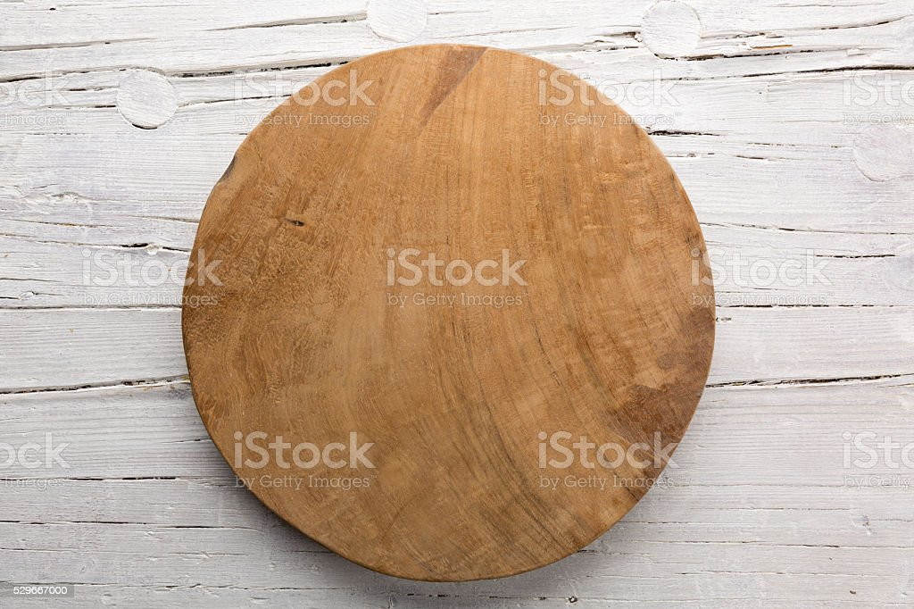 Wooden plate on white wooden background. stock photo