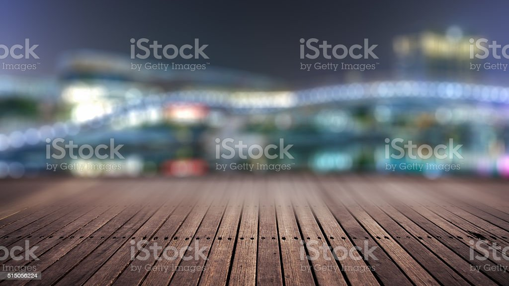 wooden platform and lights of night city stock photo