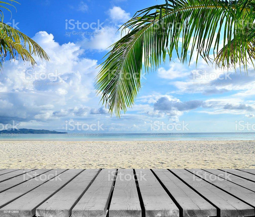 Wooden platform beside tropical sandy beach stock photo