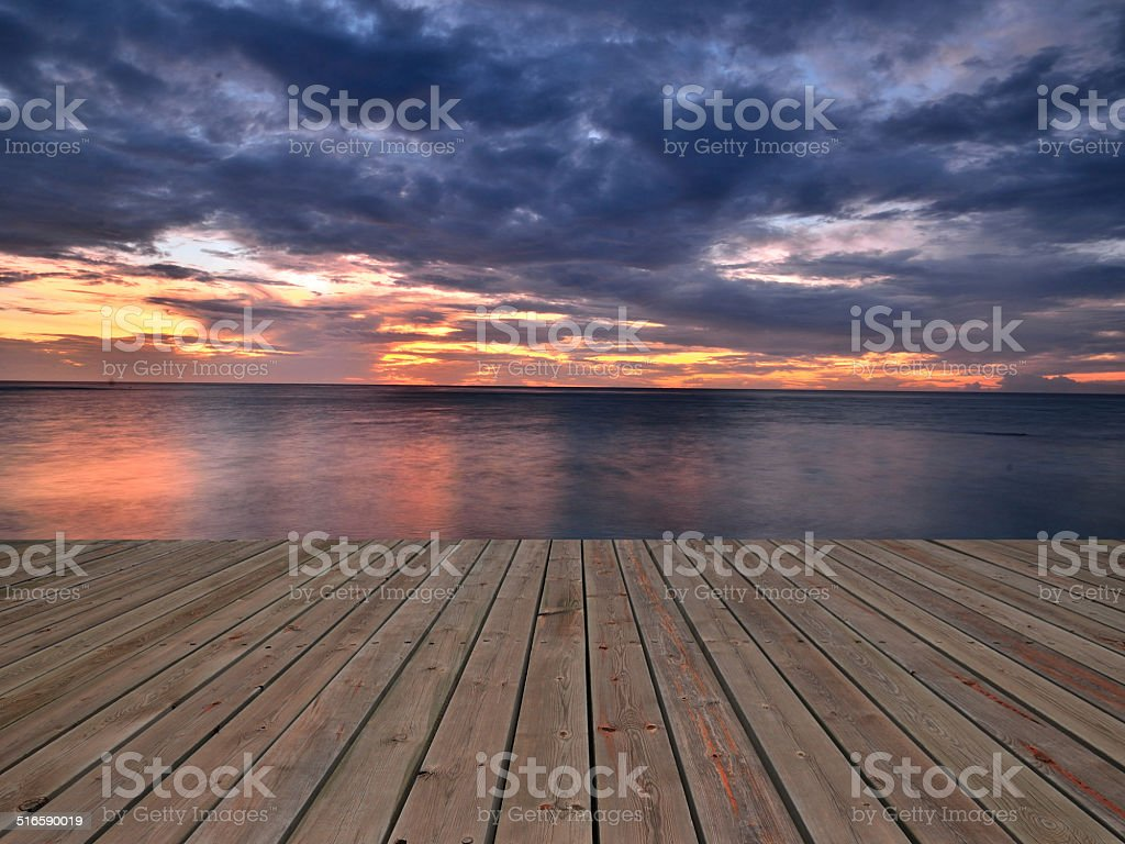 Wooden platform beside tropical sea with sunset stock photo