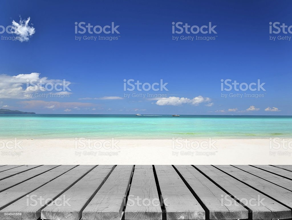 Wooden platform beside tropical white sandy beach stock photo
