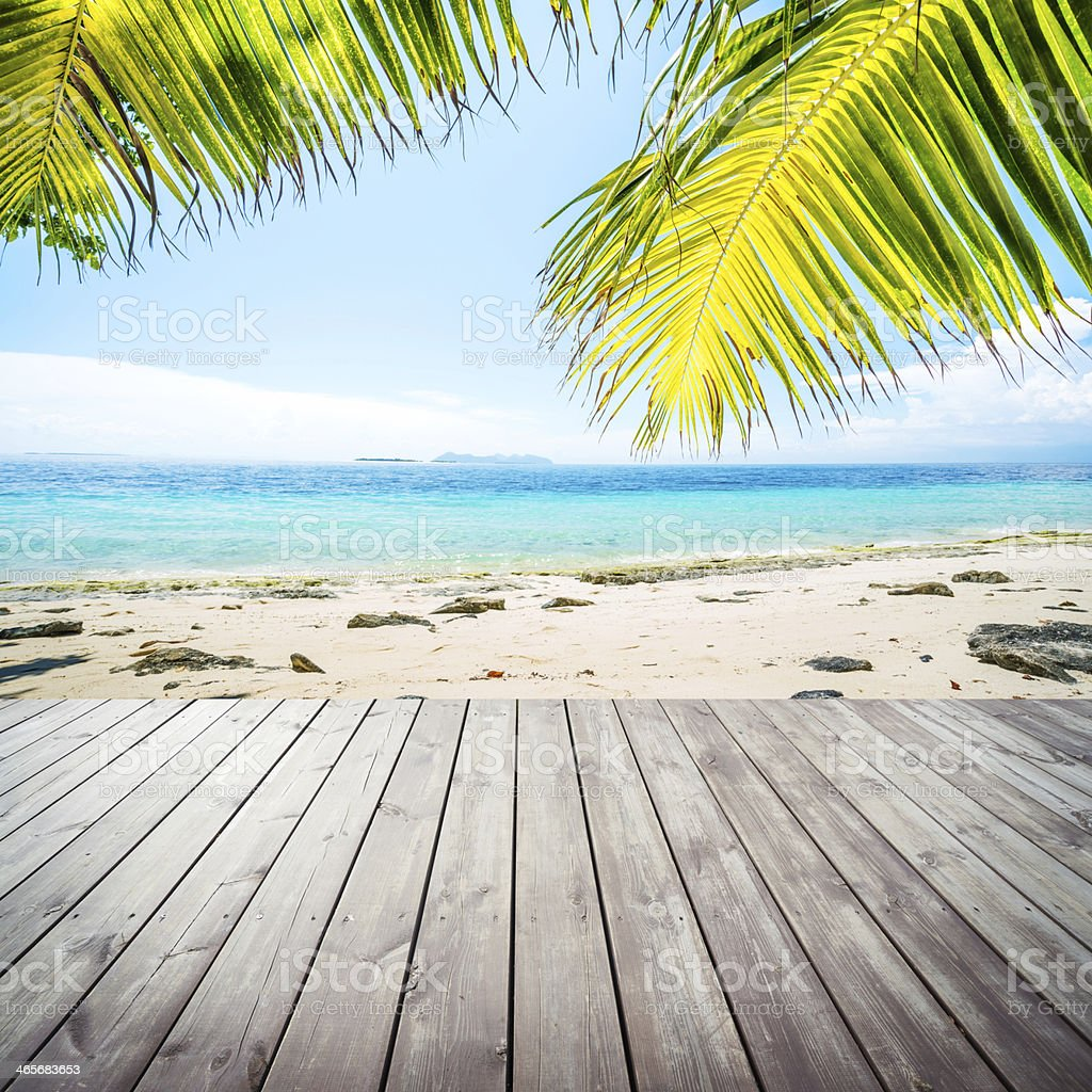 Wooden platform beside tropical beach with coconut palm stock photo