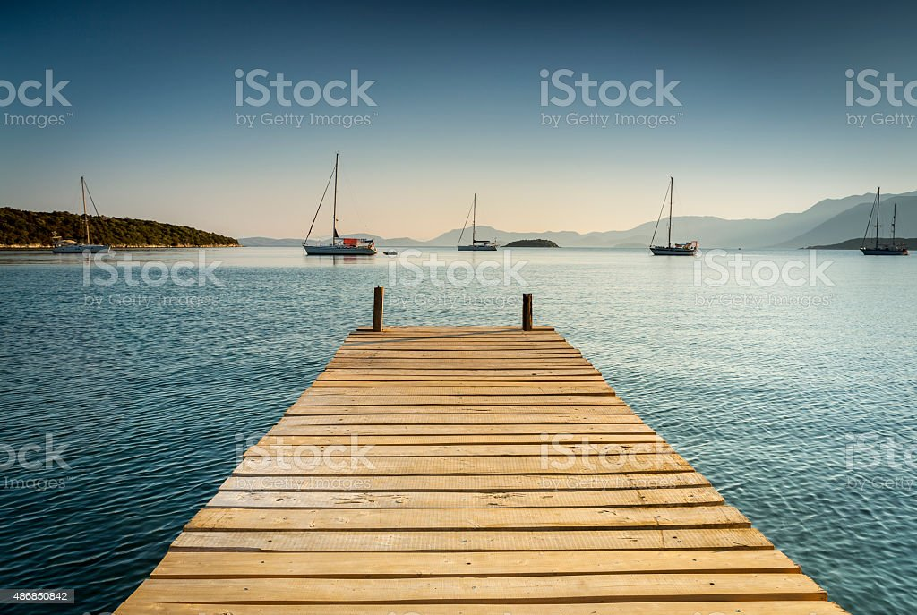 Wooden pontoon leading to the sea with sail boats stock photo