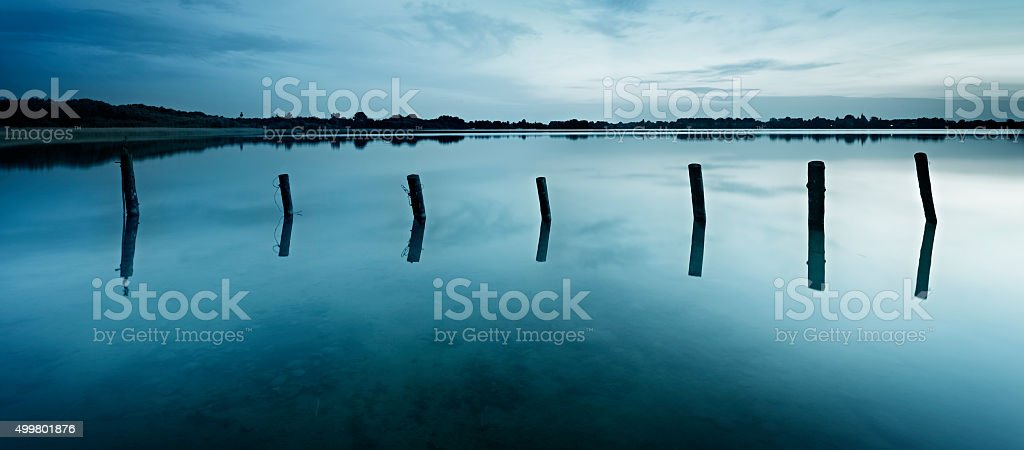 Wooden Posts in Calm Lake after Sunset, desaturated nostalgic color stock photo