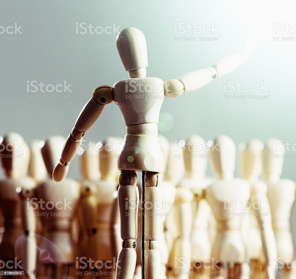 Wooden puppet addressing audience of other puppets stock photo