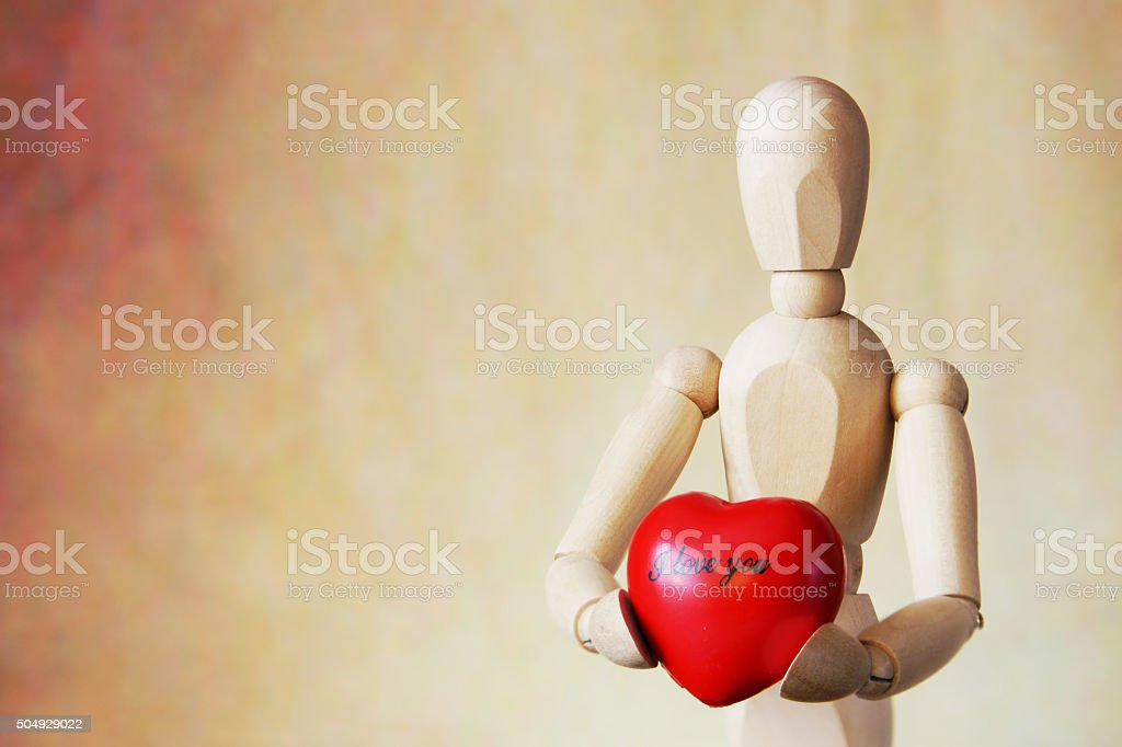 Wooden puppet holding a red heart in its hands stock photo