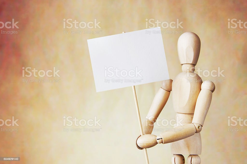 Wooden puppet holding blank white poster in its hands stock photo