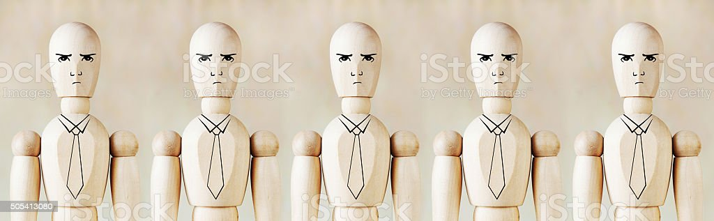 Wooden puppets as impersonal office staff stand in a row stock photo