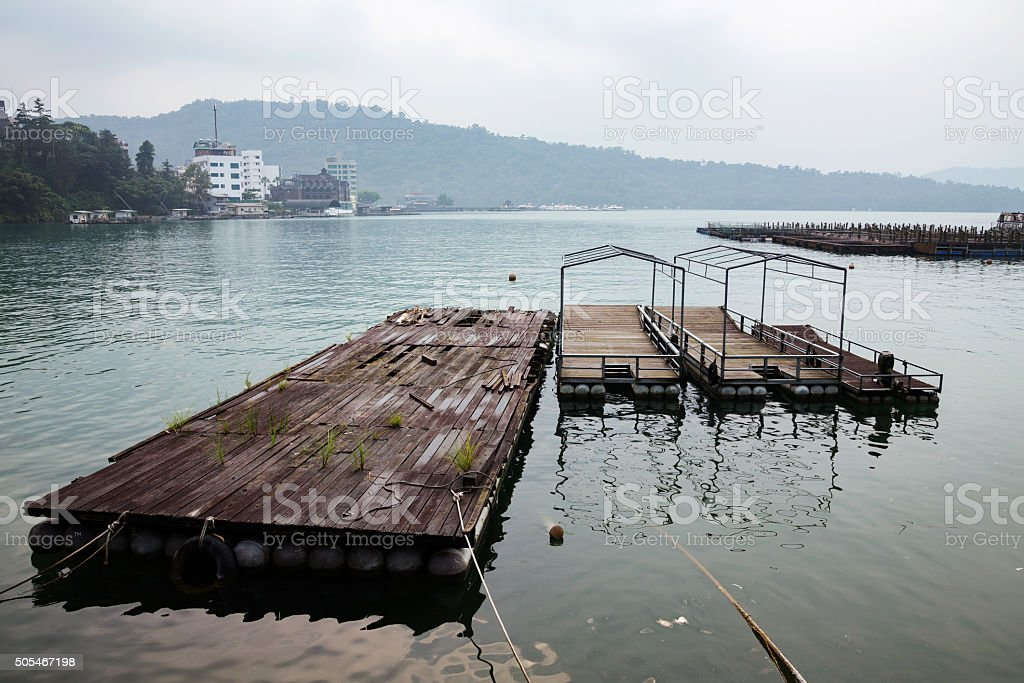 Wooden raft and boats in a lake stock photo