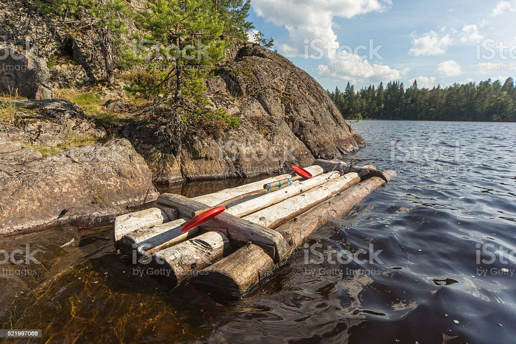 wooden raft at the rocky shore stock photo