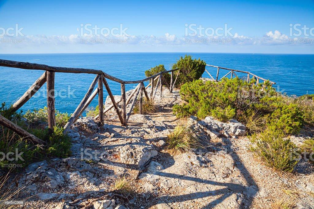 Wooden railing on rocky sea coast stock photo