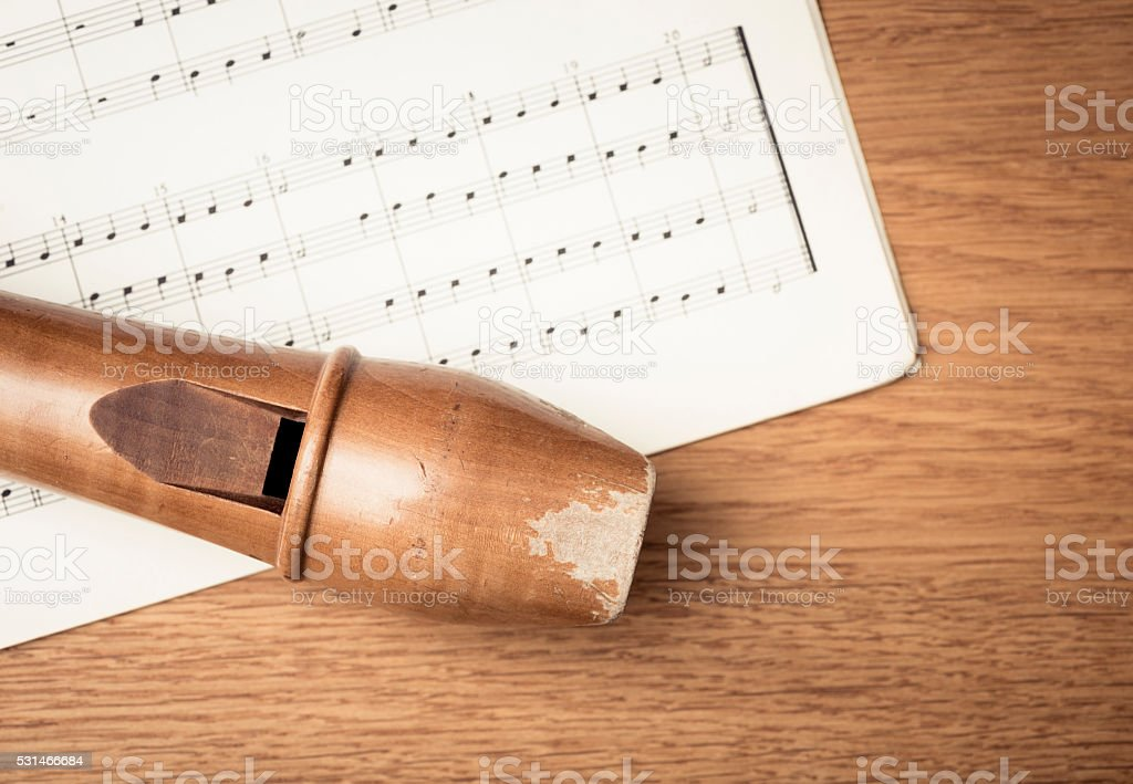 Wooden recorder and notes in close up stock photo