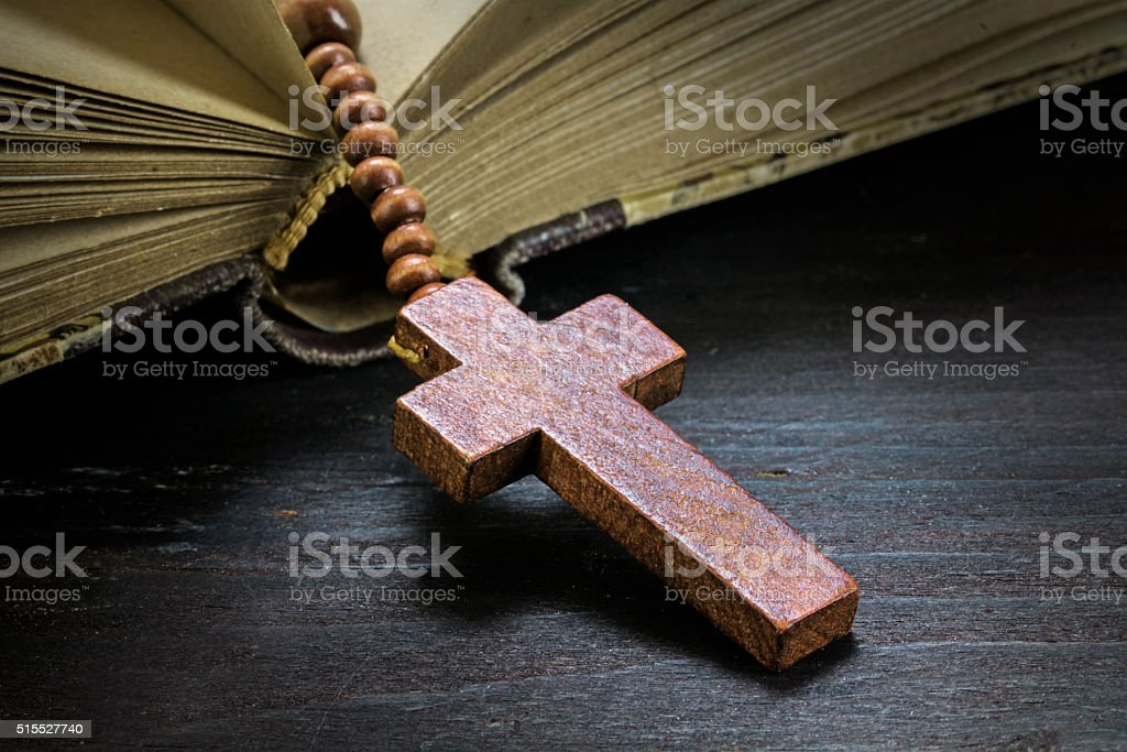 wooden rosary beads with cross in an old book stock photo