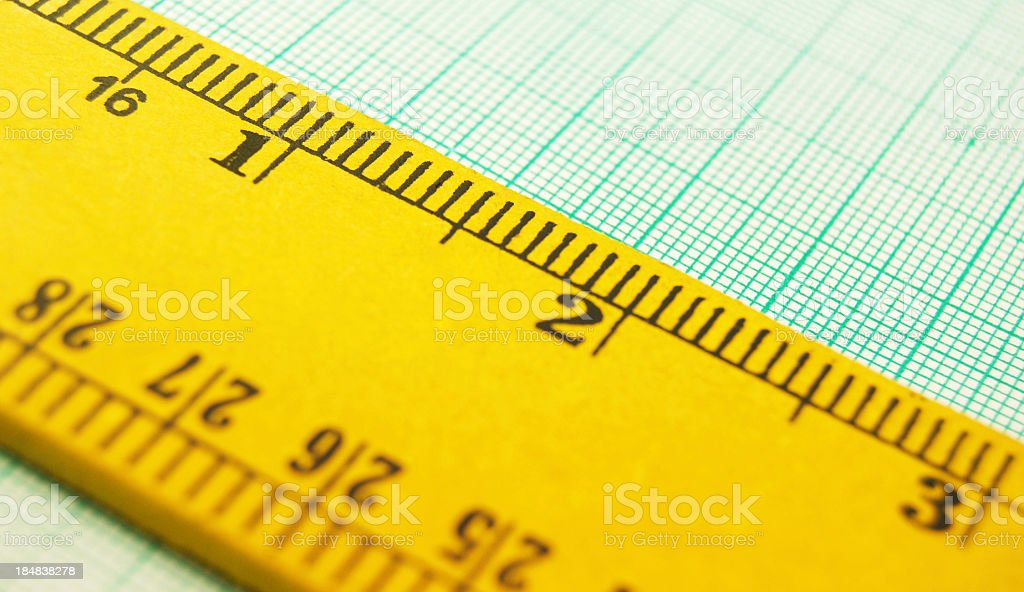 Wooden ruler on a graph paper stock photo