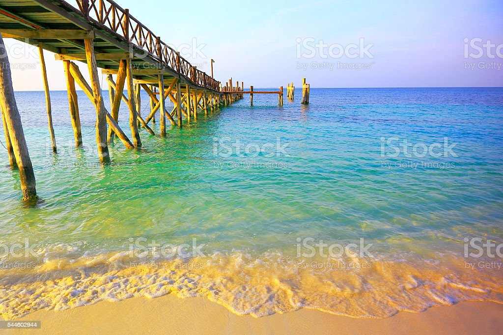 Wooden rustic píer dock over caribbean turquoise beach at sunset stock photo