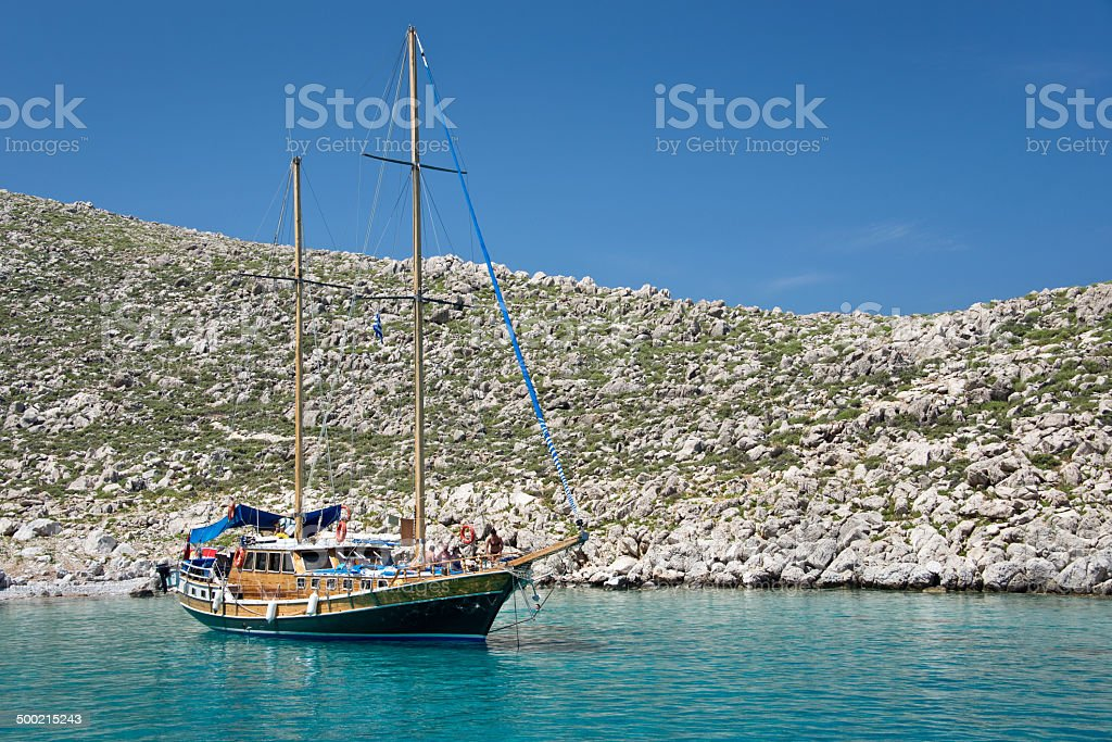 Wooden sailboat, anchored in a cove of a greek island royalty-free stock photo