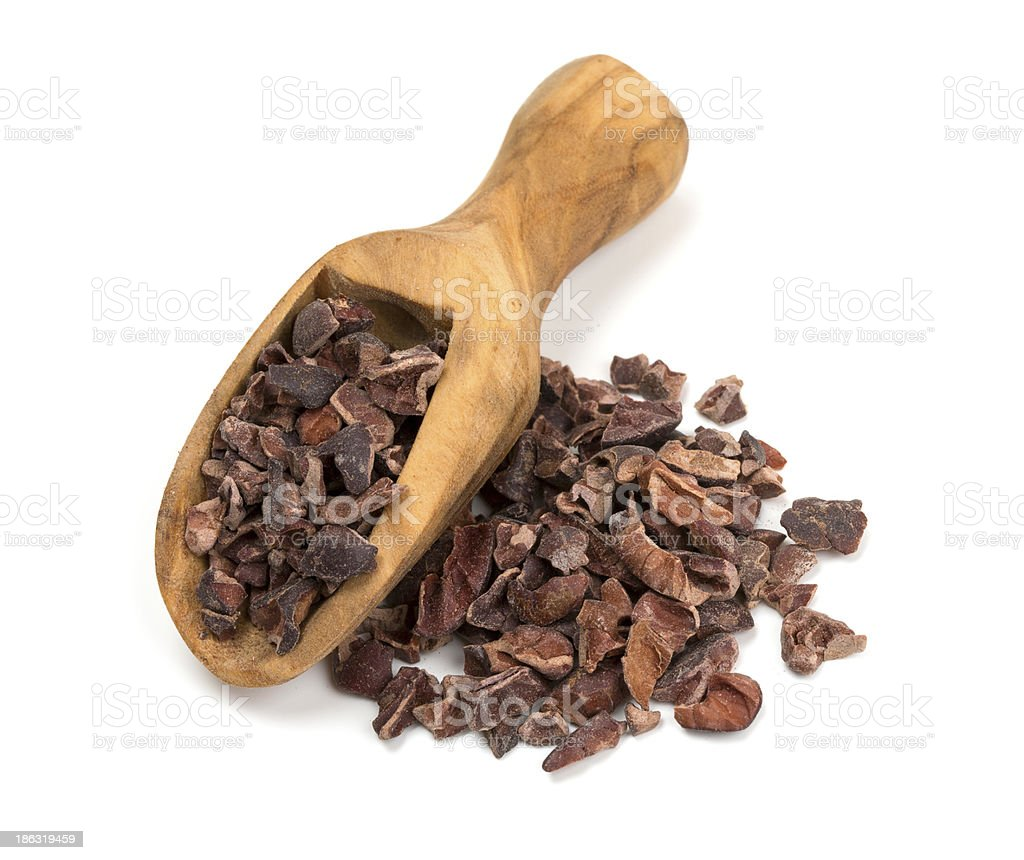Wooden scoop of cocoa nibs isolated on white background stock photo