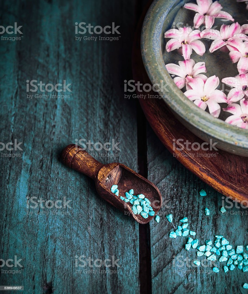 Wooden scoop with sea salt and bowl of flowers stock photo