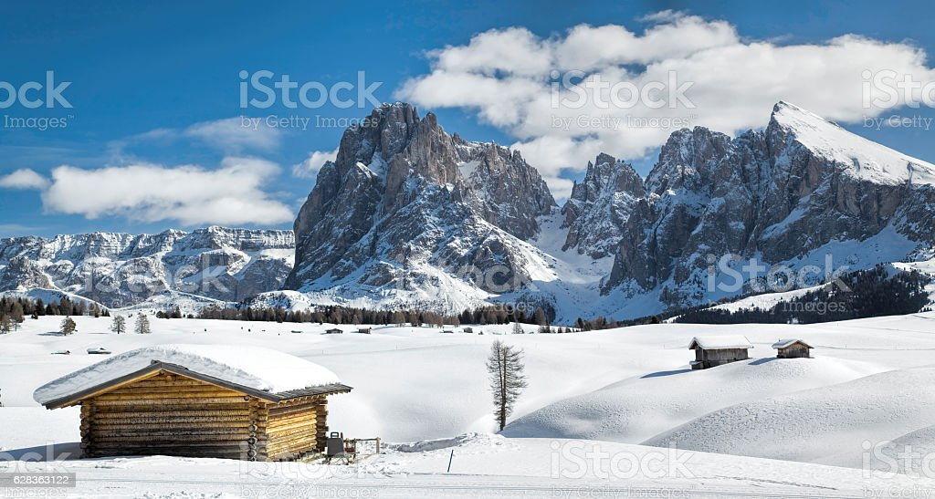 Wooden shack and Langkofel in winter landscape of Dolomites stock photo