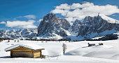 Wooden shack and Langkofel in winter landscape of Dolomites