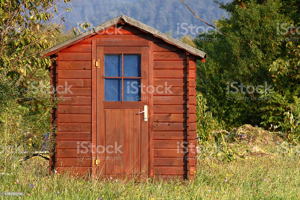 A wooden shed with a blue window stock photo