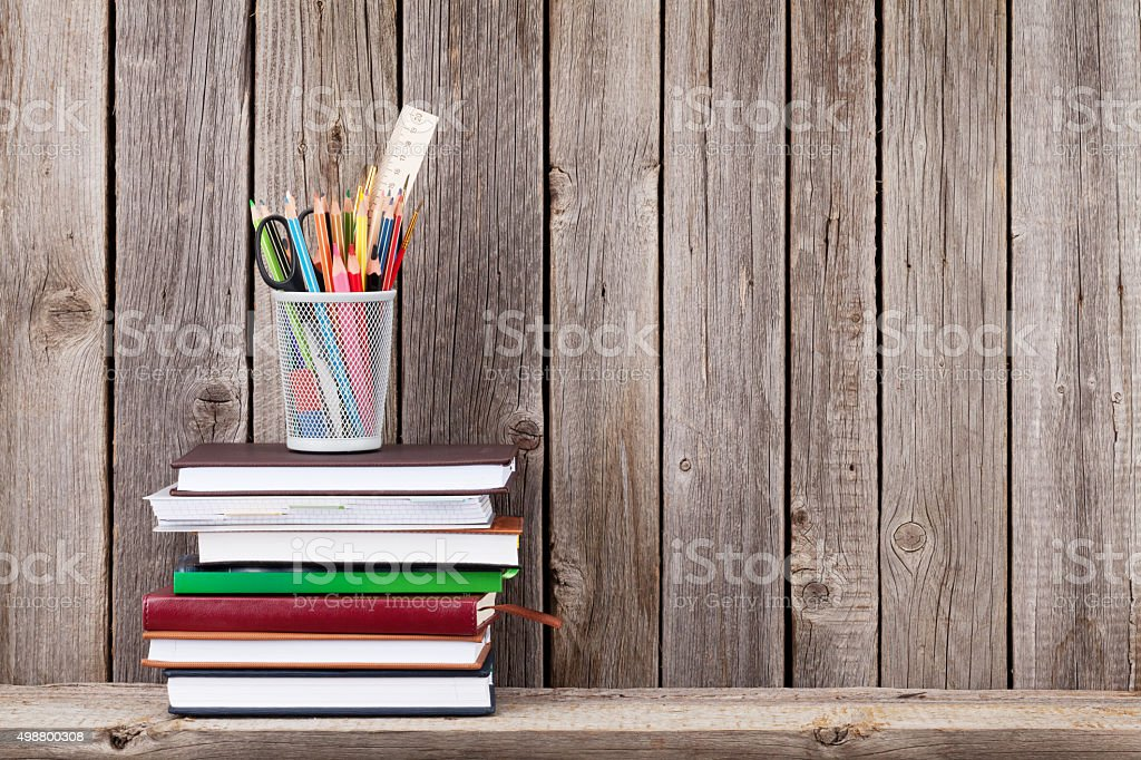 Wooden shelf with books and supplies stock photo