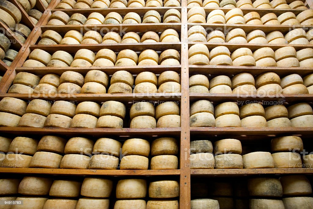 Wooden shelves of aging wheels of cheese stock photo