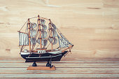 wooden ship model on wood table and wood background