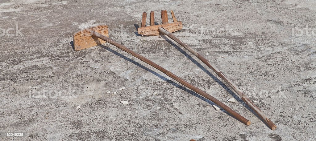 Wooden shovel and rake on the ground stock photo