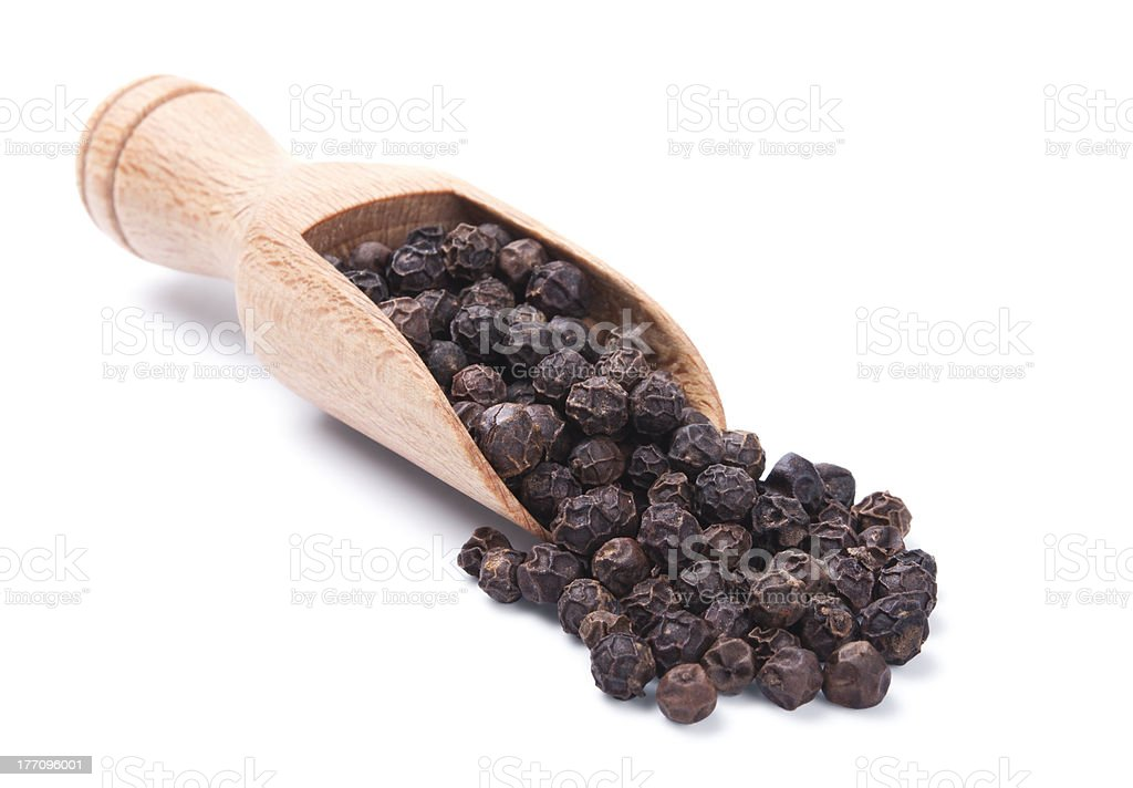 Wooden shovel with black peppercorn stock photo