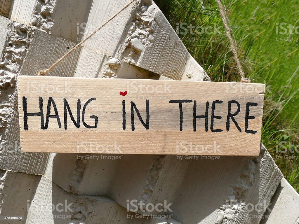Wooden sign hang in there hanging on stone wall stock photo