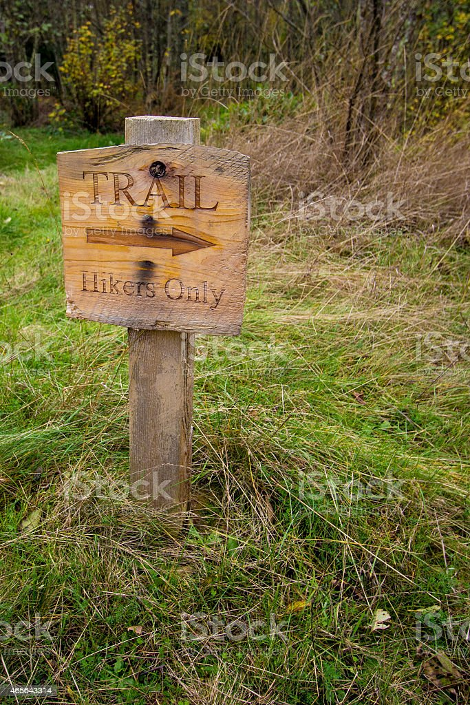 Wooden sign with arrow directing hikers to go right stock photo