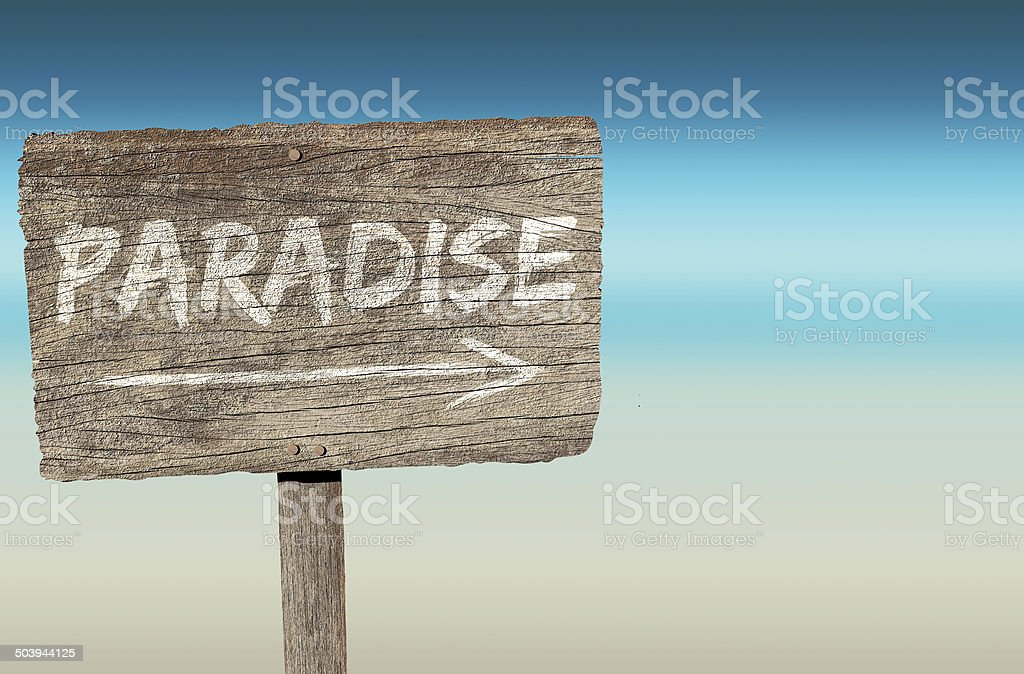 Wooden sign with paradise and an arrow drawn on it stock photo