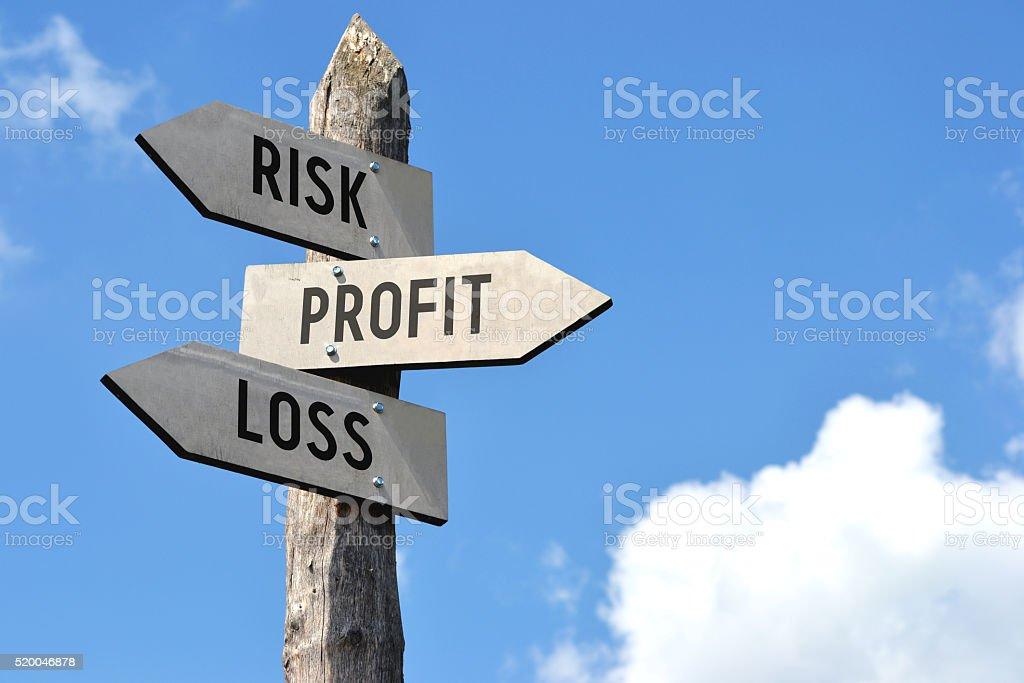 Wooden signpost - risk, profit, loss stock photo