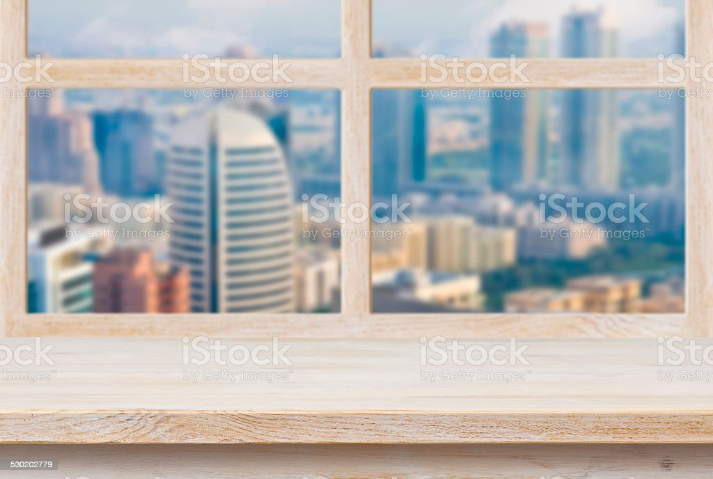 Wooden sill over blurred city view trough window stock photo