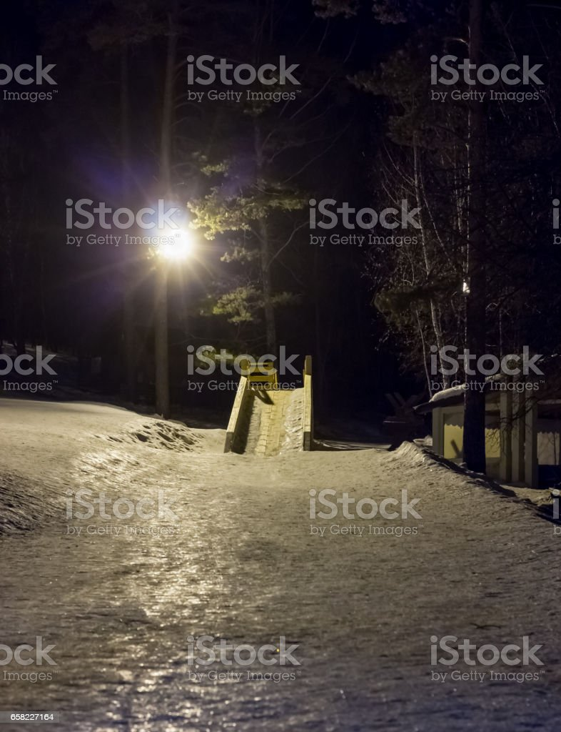 Wooden slide for skating on a winter night next to a lantern stock photo