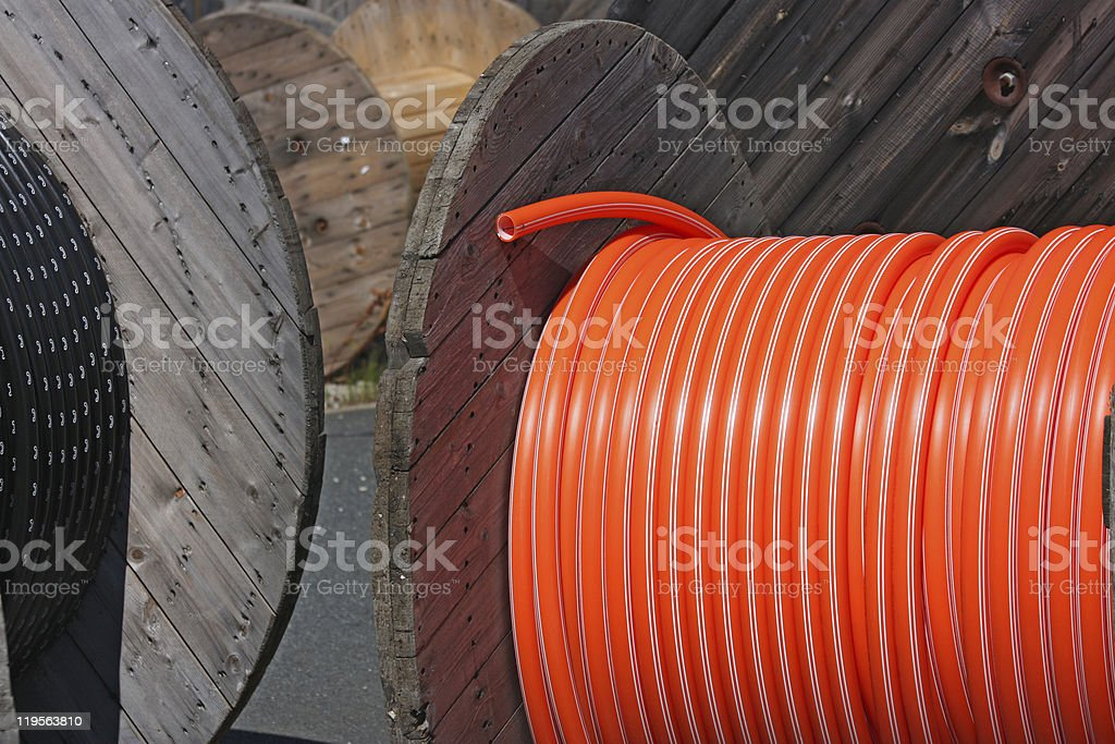 wooden spools with black and orange cables royalty-free stock photo