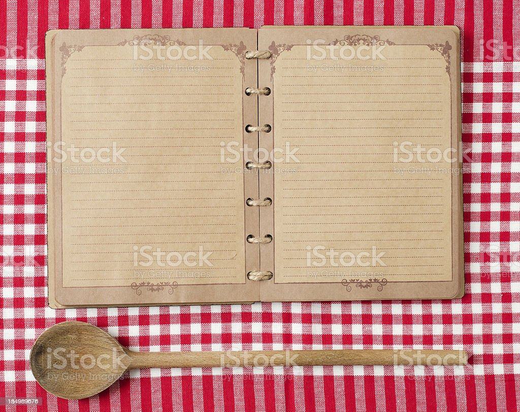 Wooden spoon and old notebook on red tableclot royalty-free stock photo